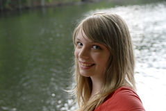 Chica joven con el lago detrás de ella Fotos de archivo
