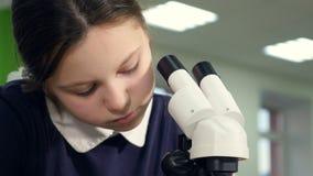 Chica joven con el microscopio en el laboratorio de investigación de la escuela que mira en el microscopio metrajes