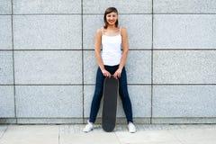 Chica joven con el monopatín en la ciudad Fotografía de archivo