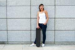 Chica joven con el monopatín en la ciudad Fotografía de archivo libre de regalías