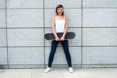 Chica joven con el monopatín en la ciudad Fotos de archivo libres de regalías
