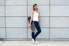 Chica joven con el monopatín en la ciudad Fotos de archivo