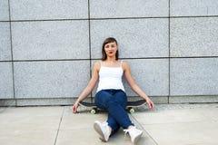Chica joven con el monopatín en la ciudad Foto de archivo