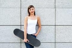 Chica joven con el monopatín en la ciudad por la sonrisa de la pared Fotos de archivo