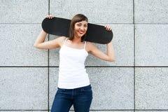 Chica joven con el monopatín en sus hombros en la ciudad por el w Imagen de archivo libre de regalías
