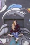 Chica joven con el monopatín en una pared del graftiti Fotos de archivo libres de regalías