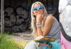 Chica joven con el monopatín que se sienta al aire libre Fotos de archivo