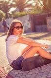 Chica joven con el monopatín que se sienta al aire libre encendido Imágenes de archivo libres de regalías