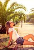 Chica joven con el monopatín que se sienta al aire libre encendido Imagenes de archivo