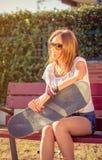 Chica joven con el monopatín que se sienta al aire libre encendido Foto de archivo libre de regalías