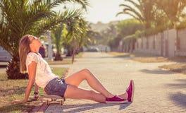 Chica joven con el monopatín que se sienta al aire libre encendido Fotos de archivo libres de regalías