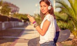Chica joven con el monopatín y los auriculares Foto de archivo libre de regalías