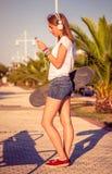 Chica joven con el monopatín y los auriculares Fotos de archivo libres de regalías
