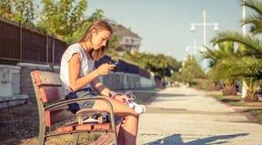 Chica joven con el monopatín y los auriculares que miran smartphone Imagen de archivo libre de regalías