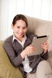 Chica joven con el ordenador de la tablilla de tacto Fotografía de archivo
