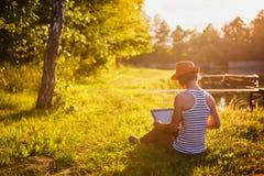 Chica joven con el ordenador portátil al aire libre Imagen de archivo libre de regalías