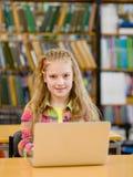 Chica joven con el ordenador portátil en biblioteca Imagenes de archivo