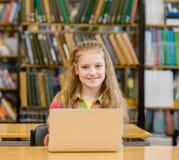Chica joven con el ordenador portátil en biblioteca Foto de archivo