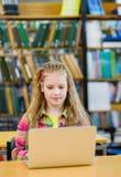 Chica joven con el ordenador portátil en biblioteca Imágenes de archivo libres de regalías