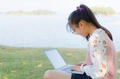 Chica joven con el ordenador portátil en la hierba Imágenes de archivo libres de regalías