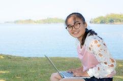 Chica joven con el ordenador portátil en la hierba Foto de archivo libre de regalías