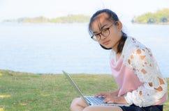 Chica joven con el ordenador portátil en la hierba Fotos de archivo libres de regalías