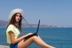 Chica joven con el ordenador portátil, en pantalones cortos y el sombrero blanco Foto de archivo
