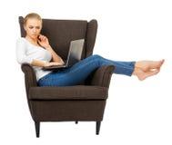 Chica joven con el ordenador portátil en silla Foto de archivo