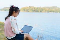 Chica joven con el ordenador portátil que se sienta en el riverbank Foto de archivo libre de regalías