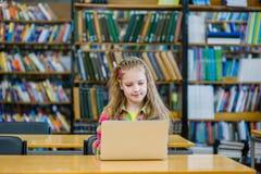 Chica joven con el ordenador portátil que trabaja en biblioteca Imágenes de archivo libres de regalías