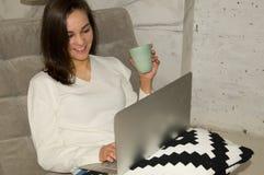 Chica joven con el ordenador portátil y la taza Fotos de archivo