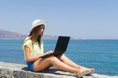 Chica joven con el ordenador portátil, en pantalones cortos y el sombrero blanco Fotos de archivo