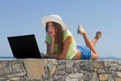 Chica joven con el ordenador portátil, en pantalones cortos y el sombrero blanco Fotos de archivo libres de regalías