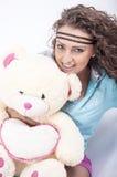 Chica joven con el oso suave en pijamas Imagen de archivo