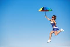Chica joven con el paraguas que salta en el cielo Fotografía de archivo
