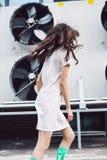 Chica joven con el pelo del vuelo en el vestido blanco de la parte posterior Imagenes de archivo