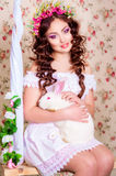 Chica joven con el pelo largo con el conejo blanco Fotos de archivo