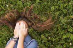 Chica joven con el pelo largo despeinado que miente en la hierba verde que cubre su cara con sus manos Foto de archivo libre de regalías