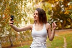 Chica joven con el pelo largo en el parque con el teléfono móvil Imagen de archivo libre de regalías
