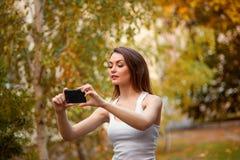 Chica joven con el pelo largo en el parque con el teléfono móvil Imágenes de archivo libres de regalías