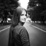 Chica joven con el pelo largo que se coloca en el camino Fotografía de archivo