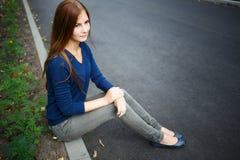 Chica joven con el pelo largo que se sienta en el camino Imagen de archivo libre de regalías