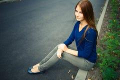 Chica joven con el pelo largo que se sienta en el camino Imagenes de archivo