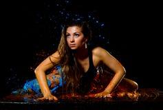 Chica joven con el pelo mojado en espray de la pintura azul y anaranjada Imágenes de archivo libres de regalías