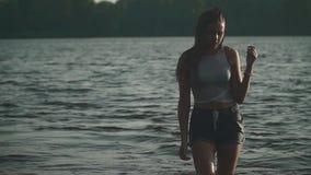 Chica joven con el pelo mojado en la orilla del río metrajes