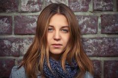 Chica joven con el pelo recto marrón al lado de la pared de ladrillo Fotos de archivo