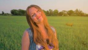 Chica joven con el pelo recto que camina en un campo verde en la puesta del sol Tiro medio Relájese en naturaleza Cámara lenta almacen de metraje de vídeo