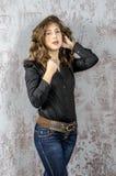 Chica joven con el pelo rizado en una camisa negra, vaqueros y un estilo occidental del alto vaquero de las botas Imagen de archivo