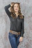 Chica joven con el pelo rizado en una camisa negra, vaqueros y un estilo occidental del alto vaquero de las botas Foto de archivo libre de regalías