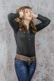 Chica joven con el pelo rizado en una camisa negra, vaqueros y un estilo occidental del alto vaquero de las botas Imagen de archivo libre de regalías